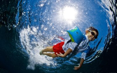 Boy jumping into water with sunburst underwater